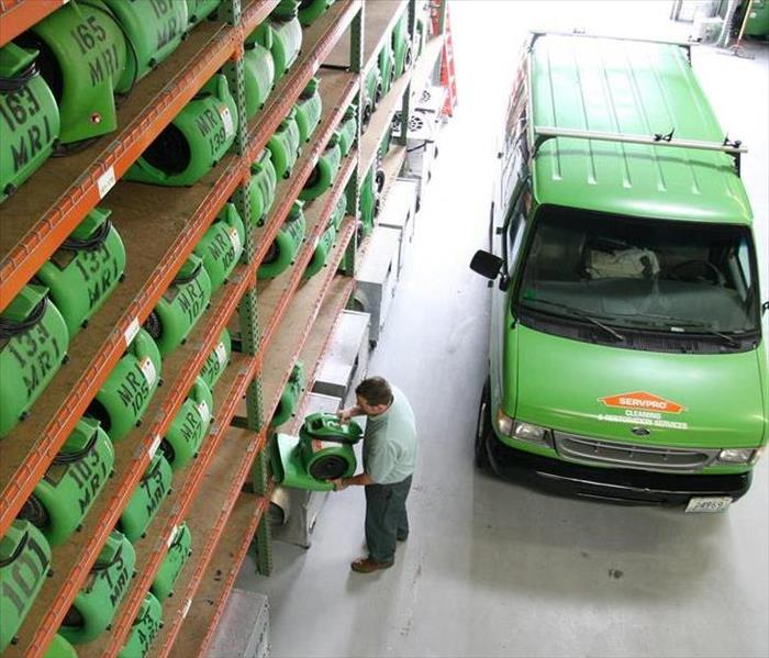 SERVPRO worker is taking an airmover down from shelves full to the ceiling of equipment to put in his box truck.