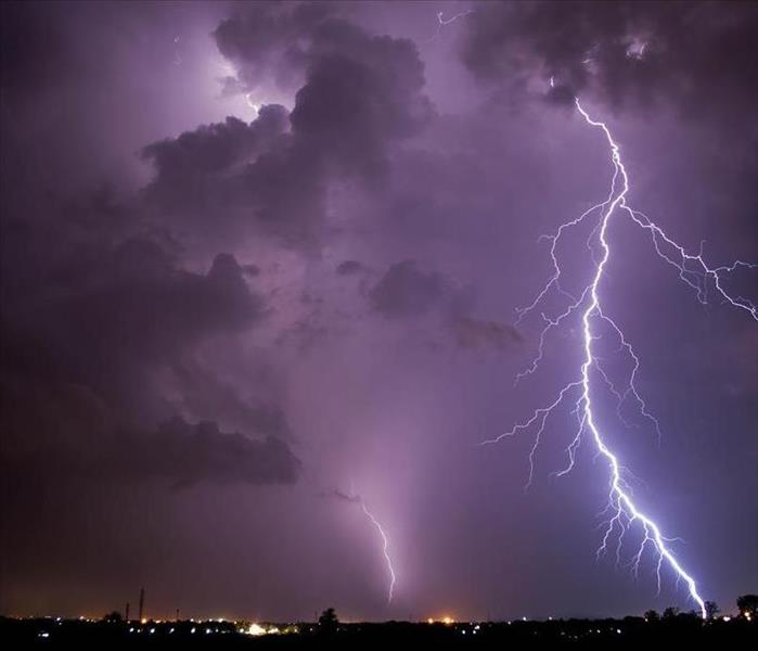 Large, dark and purple clouds fill the sky. Two large lightning strikes hit the ground.